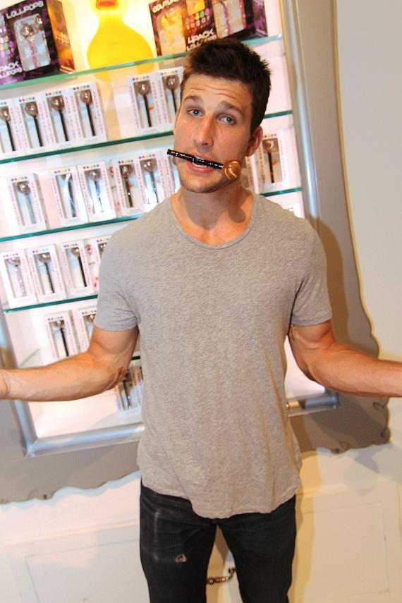 Parker Young posing with Sugar Factory's signature couture pop inside the retail store