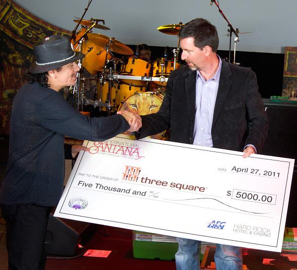 Hard Rock Hotel & Casino Vice President of Entertainment Paul Davis presents Carlos Santana with the check