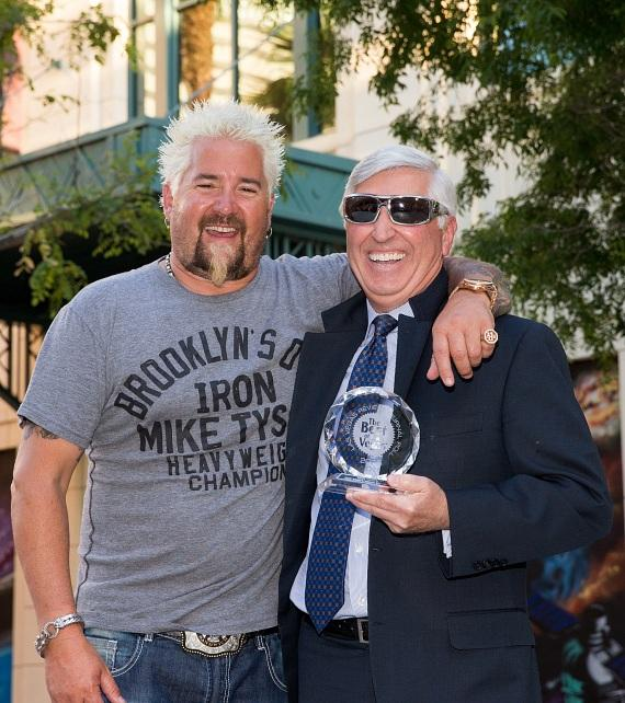 "Guy Fieri posing with President of Hospitality Bob Morse and his Best of Las Vegas ""Best Gastropub"" award"