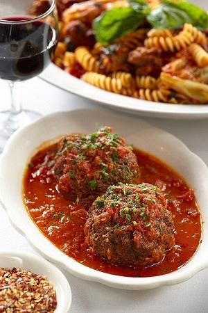 Rao's famous meatballs paired with a dish of cabbage, hot and sweet Italian sausage in San Marzano tomato sauce, over fusili pasta.