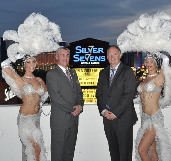 Silver Sevens Hotel & Casino Vice President and General Manager, David Nolan, and Affinity Gaming's Senior Vice President of Nevada Operations, Loren Gill, pose with classic Las Vegas showgirls after the lighting of the property's new marquee