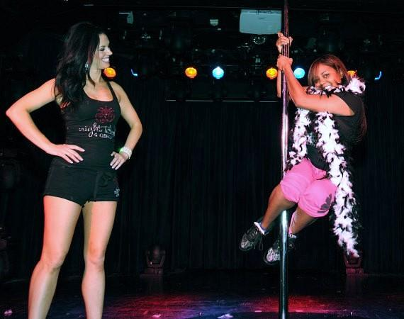 Tracey looks on as Shar Jackson practices pole dancing