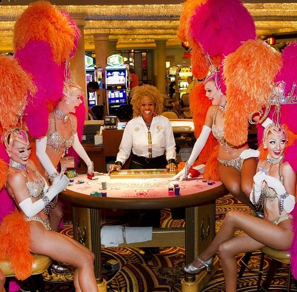 """Showgirls from Bally's hit show """"Jubilee!"""" play a hand at a signature pink table at Caesars Palace in honor of Breast Cancer Awareness month"""