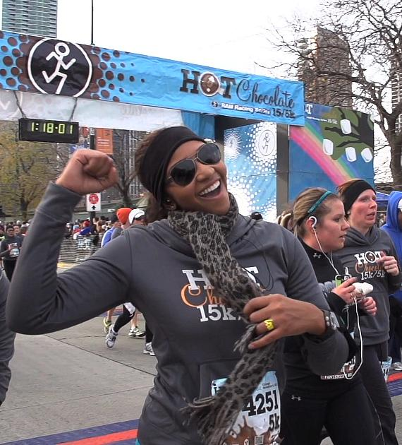 A runner crosses the finish line in a Hot Chocolate 15k/5k Race