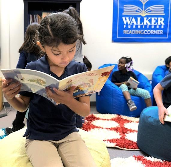 Walker Furniture - student enjoying new Reading Corner at Ira J. Earl Elementary School