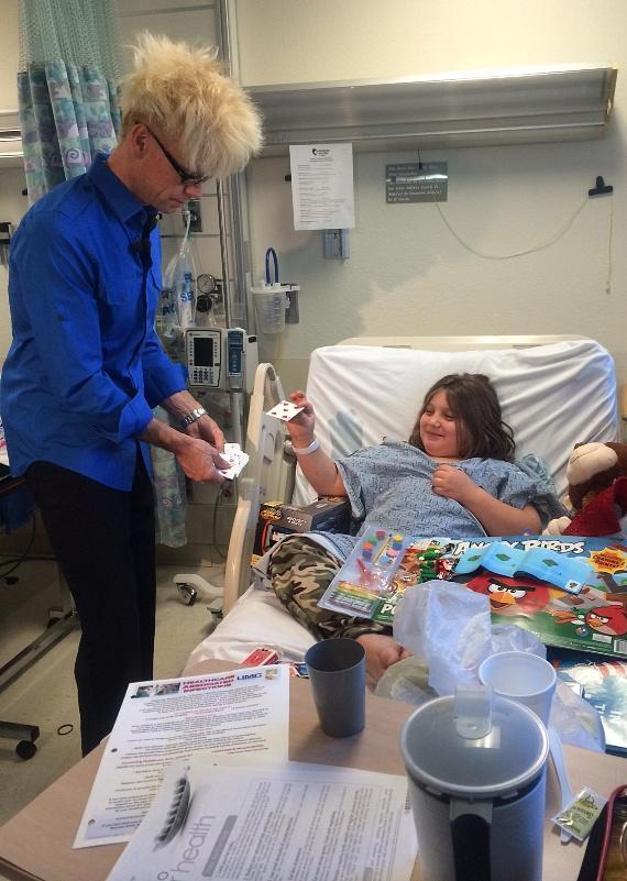 Murray performs magic for a child at Children's Hospital of Nevada at UMC