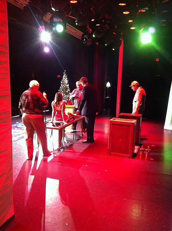 A backstage peek as magician Mark Bennick saws a woman in half with some help from audience members.