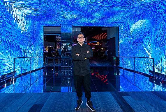 Digital artist Refik Anadol stands in front of his digital art installation DATALAND: LINQ, found throughout The LINQ's casino interior and exterior.