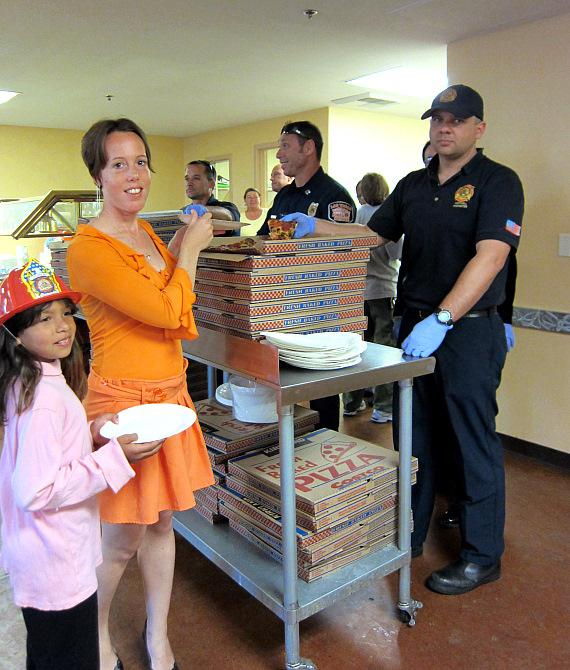 Meredith Rodriguez and Michelle Powell stand in line to be served pizza by firefighters at The Shade Tree